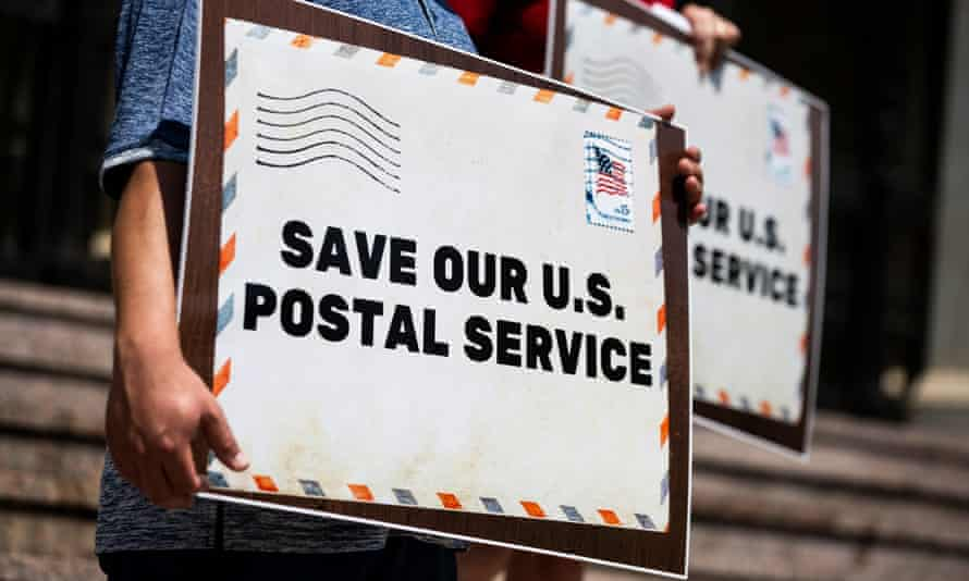 Protesters hold placards during a press conference in front of the post office, in Pasadena, California.