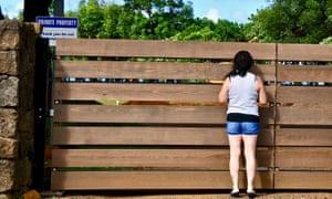 Shannon Buckner peers through the gate surrounding Mark Zuckerberg's Kauai estate.