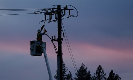 In this 26 November 2018, file photo, a Pacific Gas & Electric lineman works to repair a power line in fire-ravaged Paradise, California.