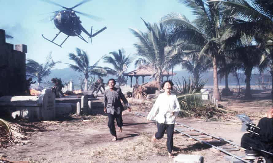 Extras run from a helicopter during filming