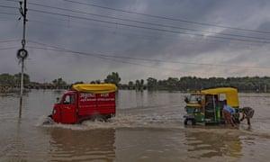 Two rickshaws on a flooded street