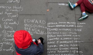 A child writes names with chalk at a protest in Dublin