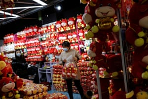 A woman wearing a face mask holds a bag of stuffed toys at a market selling Spring Festival ornaments ahead of the Chinese Lunar New Year festivity, in Beijing, China on 27 January, 2021.