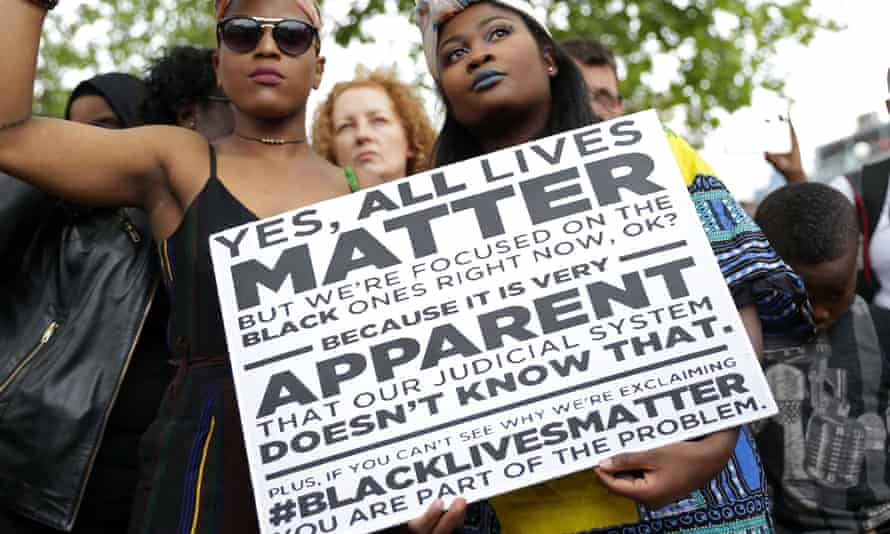 Two women hold a sign at a protest against police brutality in the US.