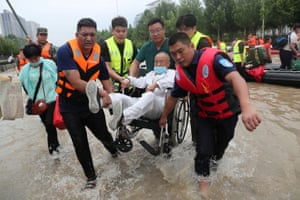 Zhengzhou, China. Rescue workers transfer a patient in a wheelchair at the Fuwai Central China cardiovascular hospital which was flooded following heavy rainfalls