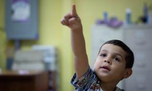 Keydiel points to a blackboard inside a classroom of the school he attends.