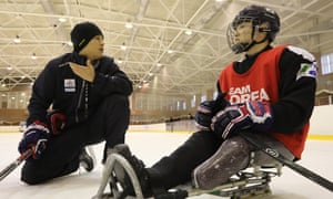South Korean para ice hockey player Choi Kwang-hyouk, right, receives instruction on the ice.