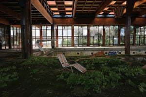 A lawn chair remains as nature takes over the indoor pool area of the long-closed Grossinger's Catskill Resort Hotel in Liberty, New York, 2012