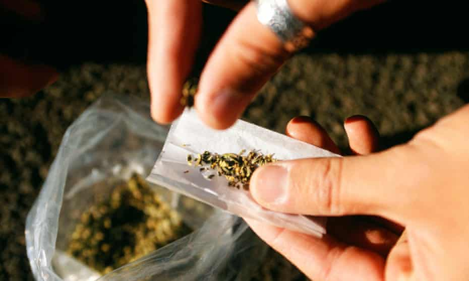 A person rolls a joint using a synthetic cannabinoid