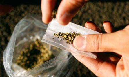 An addict rolls a joint using a synthetic cannabinoid