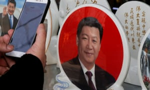 A man takes pictures of souvenir plates featuring a portrait of Chinese President Xi Jinping .