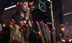 People offer prayers during a vigil in Hong Kong in memory of four youths who took their lives in recent anti-government protests.