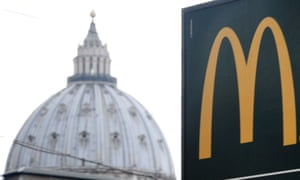 A sign for the Vatican's first McDonald's restaurant, seen with the cupola of St Peter's in the background.