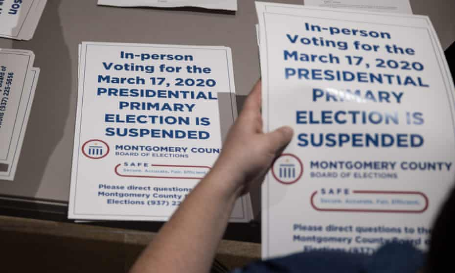 County election workers hand out election delayed signs to put up at polling stations in Dayton, Ohio on Tuesday after the primaries were canceled.