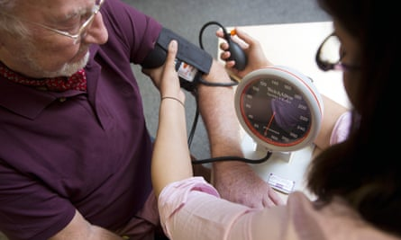 Older man getting blood pressure checked in GP's surgery