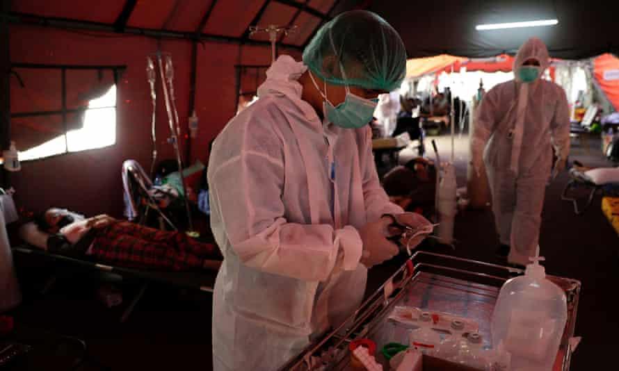 Petugas kesehatan membantu pasien Covid19 di tenda sementara di luar departemen A&E sebuah rumah sakit di pinggiran Jakarta