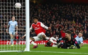 Arsenal's Reiss Nelson bundles the ball over the line.