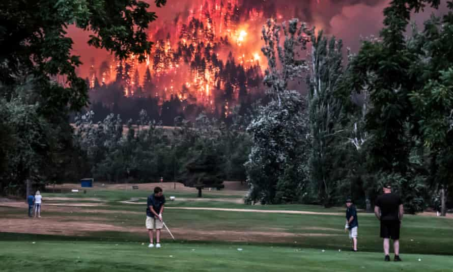The Eagle Creek wildfire burns as golfers play at the Beacon Rock golf course in Washington state on 4 September.