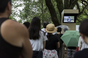 Attendees watch a speech by prime minister Shinzo Abe