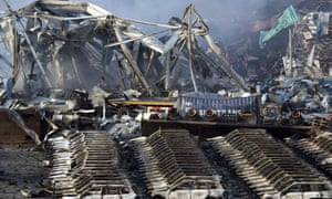 Charred remains of a warehouse and new cars are left burned after explosions at a warehouse.