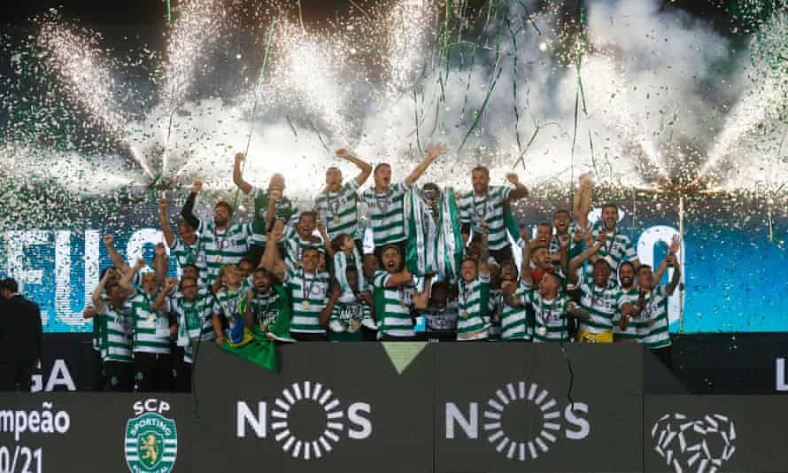 Sporting's players celebrate winning their first Primeira Liga since 2002 by lifting the trophy while fireworks go off in the background.