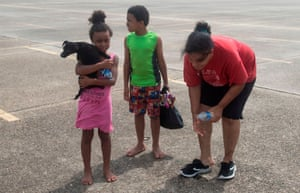 A family takes a break after getting off a National Guard truck when they were evacuated from their home, following the passing of Hurricane Laura in Lake Charles, Louisiana.