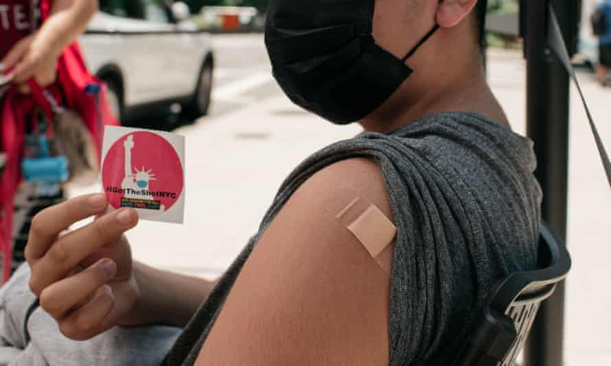 A 14-year-old vaccinated against Covid-19 holds up a sticker at a pop-up vaccination site in Queens, in New York City.
