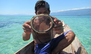 A Bajau diver holding up a traditional wooden diving mask.