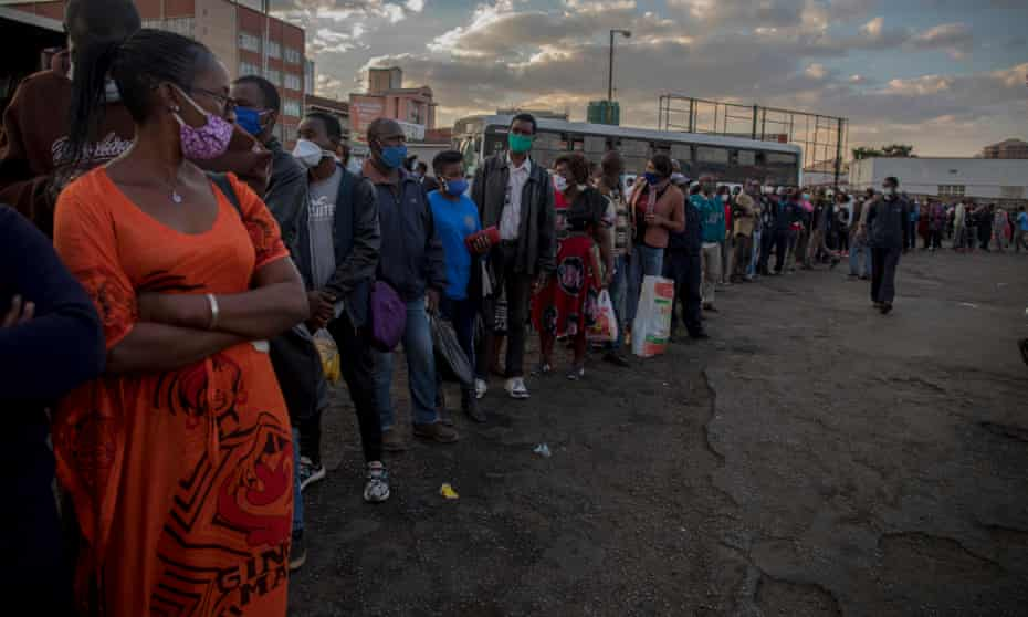 People wait in line for buses to take them home after work.