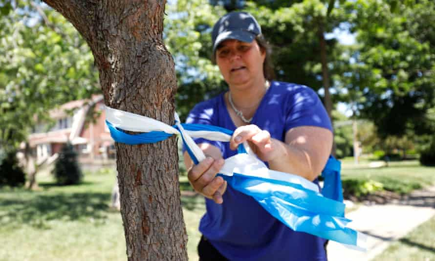 A Wyoming resident ties blue and white ribbons around a tree in preparation for Otto Warmbier's funeral.