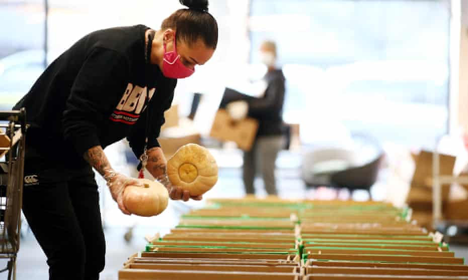A volunteer fills boxes for a food bank in Auckland, New Zealand