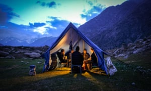 People gathered inside a tent, the front open, mountains behind, as night falls