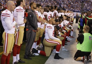 Members of the San Francisco 49ers kneel during the playing of the national anthem.