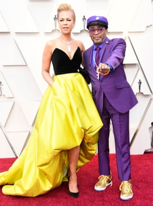 """Director Spike Lee, whose film BlacKkKlansman was nominated for best picture and best adapted screenplay, wore a purple Oswald Boateng suit with gold Air Jordan 3 """"Tinker"""" trainer, featuring with the name of his film company. He was joined by his wife Tonya Lewis Lee in a black and yellow dress. His Love/Hate rings were from his film Do The Right Thing, which the Oscars famously snubbed in 1990"""