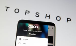 An Asos logo in a smartphone in front of a displayed TopShop logo.