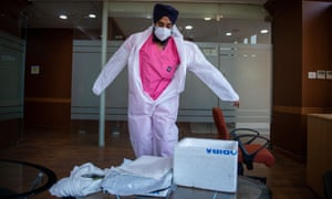 A health worker dons protective equipment in India.