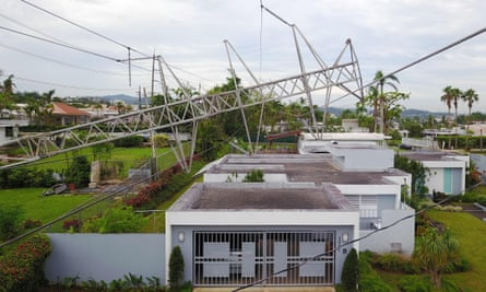 A power line tower downed by the passing of Hurricane Maria lies on top of a house in San Juan, Puerto Rico