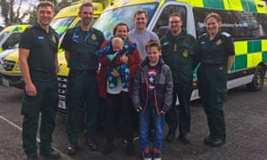 Jayne Rowland, 36, and Joshua Mogg, 29, with their newborn son, Harry, and 8-year-old son, Benjamin, and members of the South Western Ambulance Service NHS Foundation Trust