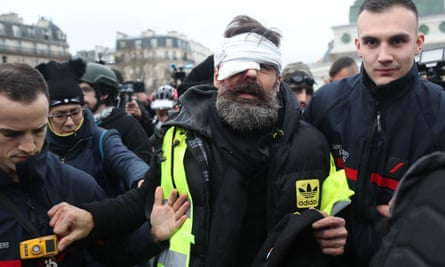 Jérôme Rodrigues, one of the leaders of the gilets jaunes movement, is helped after being injured in the eye during clashes between protesters and riot police in Paris