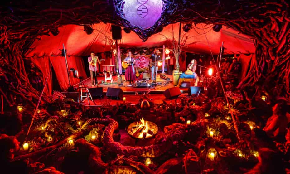 Band performs on a stage, at night, in front of an audience, illuminated by small lanterns, at the Medicine festival in Berkshire, UK, August 2021.