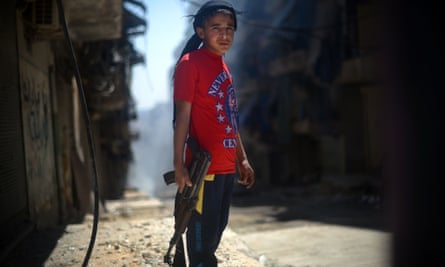 A Syrian boy holds an AK-47 assault rifle in the majority-Kurdish Sheikh Maqsud district of the northern Syrian city of Aleppo