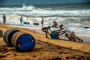 Men, women and children retrieve gasoline barrels from the Togolese coastline