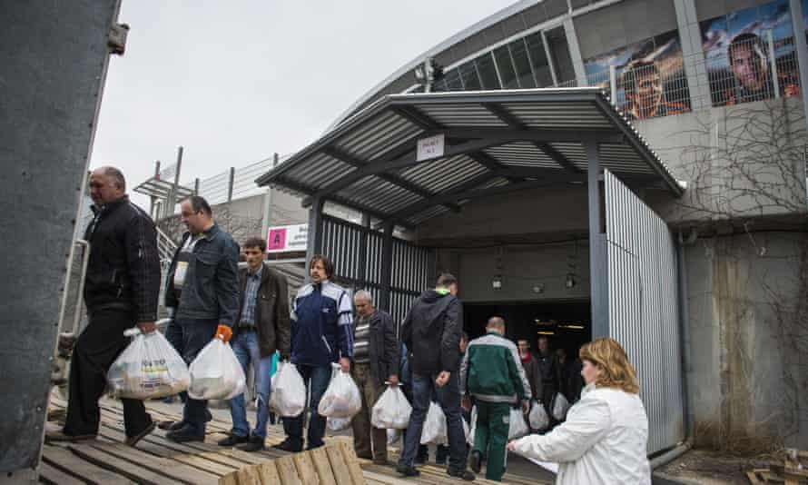 Volunteers emerge from Shakhtar's now idle stadium with food parcels last April as part of the owner Renat Akhmetov's push to help the needy across the Donetsk region.
