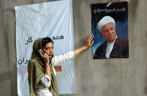 A young woman chats on her mobile phone next to a campaign poster of Ali Akbar Hashemi Rafsanjani at a rally in northern Tehran in 2005.