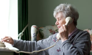A woman using a traditional telephone at home