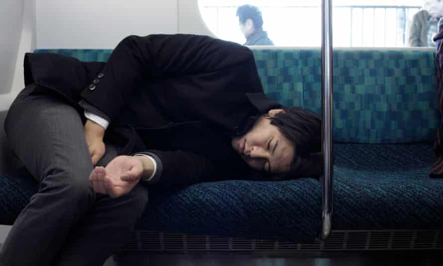 A sleeping businessman during his train commute in Japan