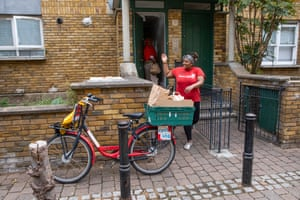 Kenosha Smith, one of the team at the Max Roach Loughborough community centre in Brixton, delivers food to the home of Shafiyo Abu.