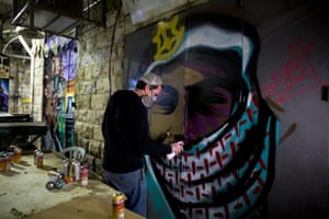 Solomon Souza spray-paints a graffiti portrait on to the shutters of a market stall