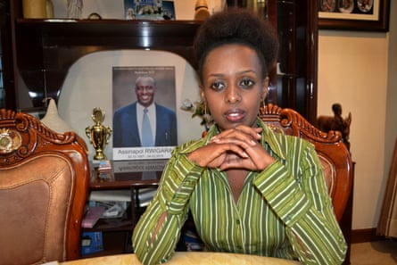 Diane Shima Rwigara sits next to a portrait of her father at her home in Kigali