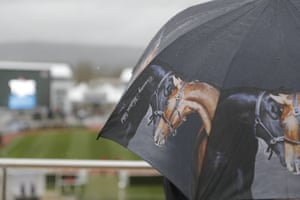 Champion Day A racegoer takes cover under a horse themed umbrella
